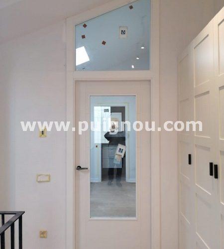 Fusteria Puignou-Porta vidriera lacada blanca amb tarja superior.