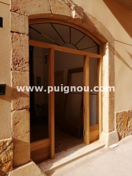Porta d'entrada de mig punt, amb fusta d'iroko, La porta s'ha realitzat al taller i posteriorment, s'ha ajustat, subministrat i col·locat.